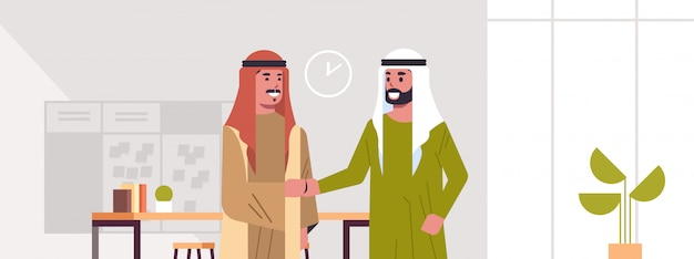 Ic businessmen handshaking arab business partners couple hand shake during meeting agreement partnership concept modern co-working center office interior portrait horizontal
