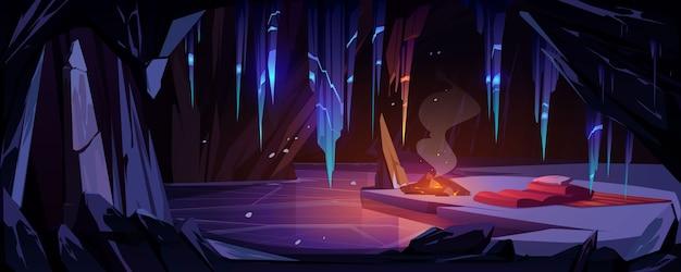 キャンプファイヤーと寝袋のある山の氷の洞窟、凍った湖とつららがぶら下がっている洞窟の観光客の夜通しの場所。結晶鍾乳石のある空の洞窟。漫画のベクトルイラスト