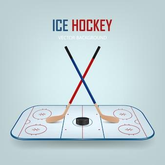 Хоккейная шайба и скрещенные клюшки на фоне хоккейного поля.