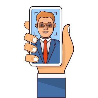 顔認識システム。顔id。スマートフォンを持っている人の手。スーツを着たビジネスマン。生体認証。