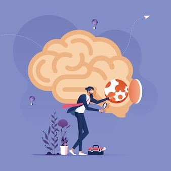 Idea research concept-businessman with magnifying glass looking inside a brain