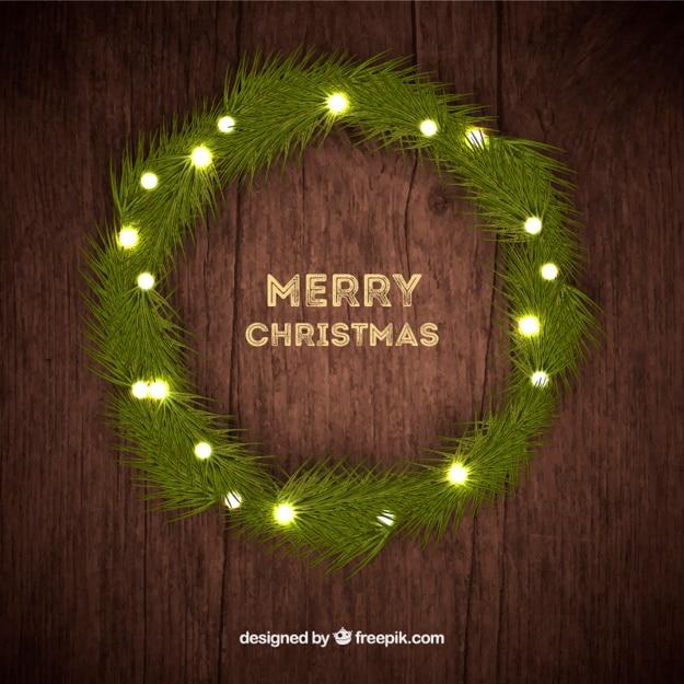 Illuminated christmas wreath on wood background