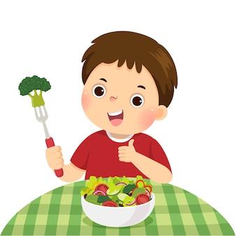 Иллюстрация мультфильм маленький мальчик ест салат из свежих овощей и показывает палец вверх знак.