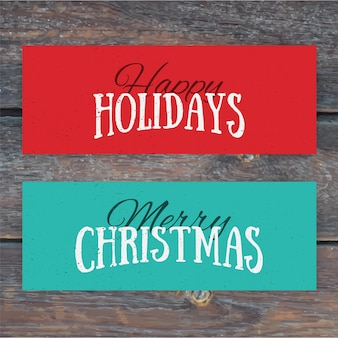Illustration of colorful paper cards with happy holidays and merry christmas lettering. christmas calligraphy on wood background.