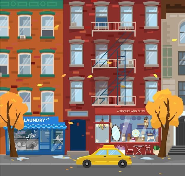秋の街並みのイラスト。市内の雨天。ランドリーや骨董品店、タクシー。黄色の木。