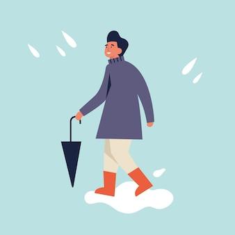 秋の服で幸せな男のイラスト。若い男が歩いて傘を保持しています。雨天。