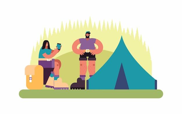 Иллюстрация мужчины и женщины, просматривающих карту на смартфоне во время отдыха возле палатки в кемпинге в сельской местности