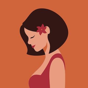В профиль красивая улыбающаяся молодая женщина с цветком в волосах.