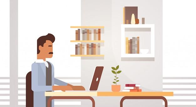 インドのビジネスマンの机に座っているラップトップコンピューター