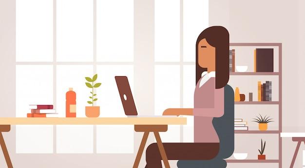インドのビジネス女性の机に座ってラップトップコンピューター実業家事務所