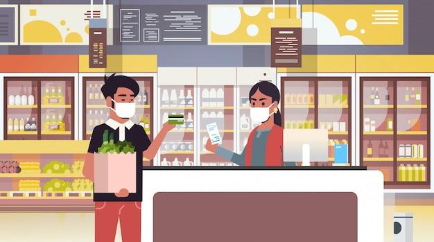 医療用防護マスクのインドのレジ係と男性の顧客検疫コロナウイルスの流行の概念人々は食料品店のスーパーマーケットのインテリアポートレート水平で商品を購入