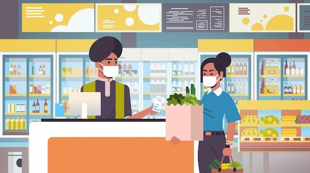 医療用防護マスクのインドのレジ係と女性の顧客検疫コロナウイルスの流行の概念人々は食料品店のスーパーマーケットのインテリアポートレート水平で商品を購入