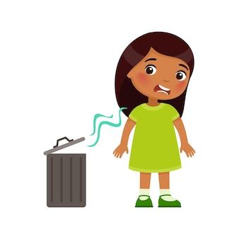 Индийская маленькая девочка не любит неприятный запах из мусорного ведра. выражение эмоций на лице.
