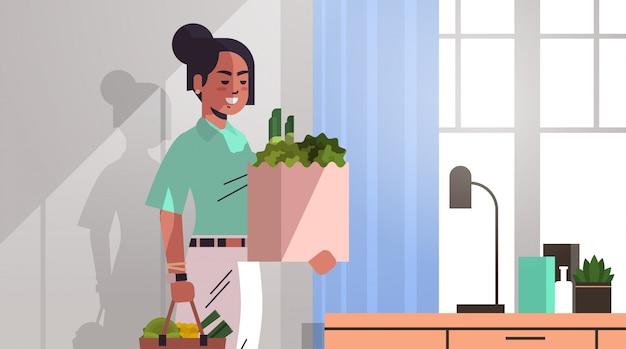 新鮮な野菜とモダンなリビングルームのインテリアの水平方向の肖像画の買い物袋を保持しているインドの女性