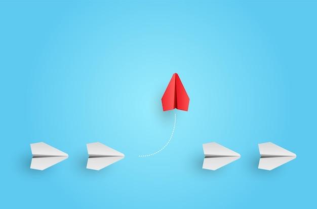 個性コンセプト。個性的でユニークなリーダーの赤い紙の飛行機が横に飛びます。