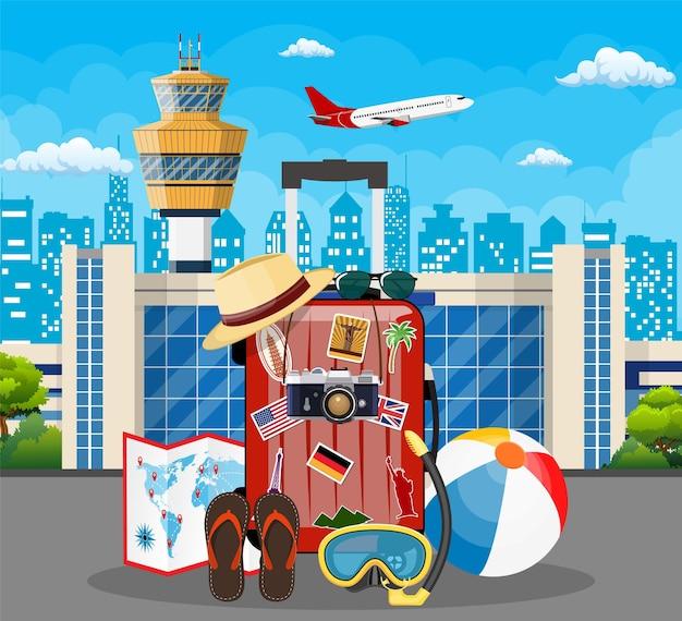 国際空港のコンセプト。世界中の国や都市のステッカーが付いた旅行スーツケース。都市の景観。フラットスタイル