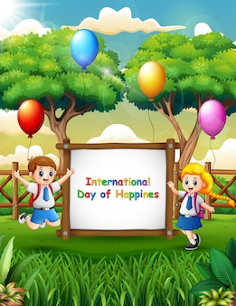 International day of happiness sign with happy school children