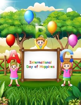 公園で陽気な子供たちと国際幸福デーのサイン