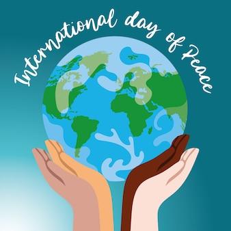 世界を持ち上げる異人種間の手による国際平和デーのレタリング
