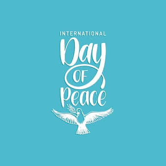 International day of peace, vector hand lettering. drawn illustration of dove with a palm branch on blue background. holiday card, poster with calligraphy.