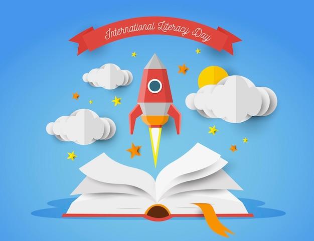 Международный день грамотности в бумажном стиле с открытой книгой и ракетой
