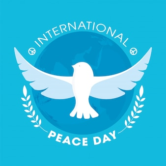 International peace day text with flying dove and leaf branches on blue earth globe background.