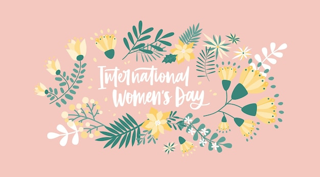 International women's day lettering handwritten with cursive font surrounded by blooming spring flowers and leaves