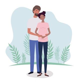 Gli amanti interrazziali accoppiano i personaggi della gravidanza nel paesaggio