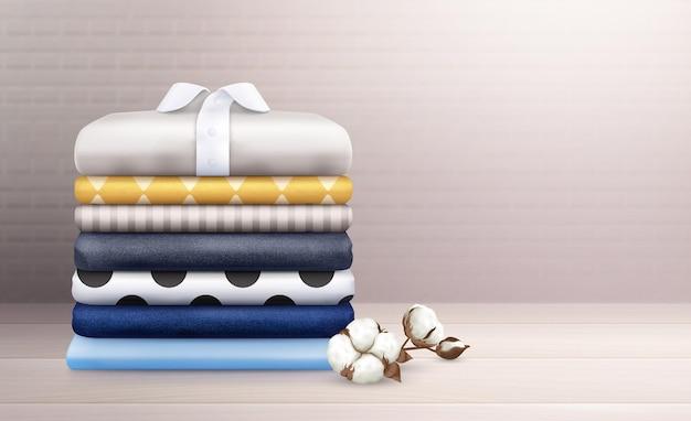 アイロンをかけた服と綿の枝で飾られたカラフルなリネンスタックリアルな構成