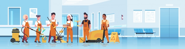 Janitors team cleaning service mix race cleaners in uniform working together with professional equipment hospital reception interior