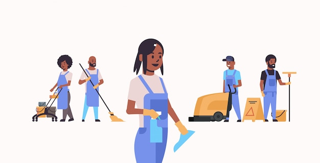 Janitors team working together cleaning service concept   male female cleaners in uniform using professional equipment  full length horizontal