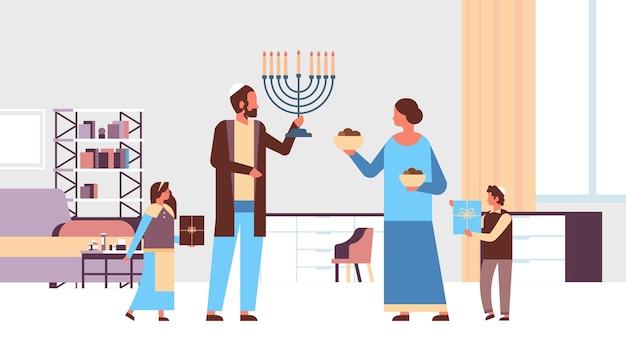 ユダヤ人の家族が本枝の燭台とギフトボックスを保持ユダヤ人の親の子供たちが伝統的な服を着て一緒に立って幸せなハヌカユダヤ教宗教的な祝日