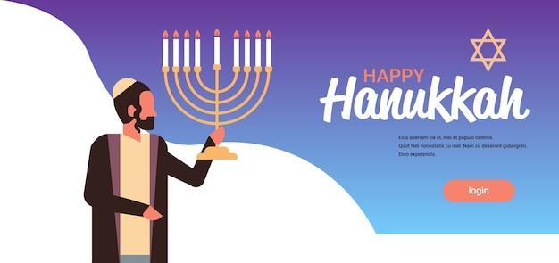 伝統的な服でメノラーユダヤ人を保持しているユダヤ人幸せハヌカ