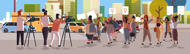 Journalists reporting breaking news from street protest activists holding placards feminist demonstration girl power movement women empowerment concept cityscape background horizontal full length