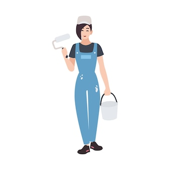 Joyful house painter or decorator wearing dungarees and holding paint roll and bucket