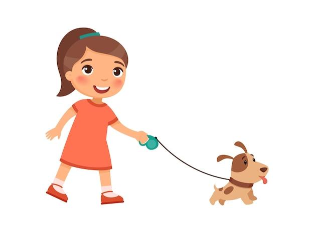 즐거운 어린 소녀는 귀여운 강아지의 가죽 끈에 걷고있다