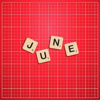 Июньский месяц прописными буквами с концепцией блока scabbles