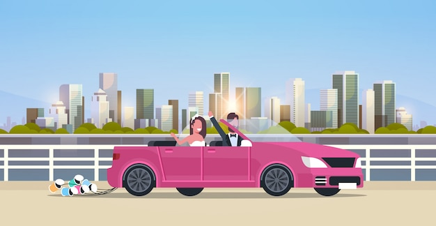 Just married bridegroom and bride on road trip driving convertible car romantic couple man woman in love wedding day concept modern urban city buildings cityscape background horizontal