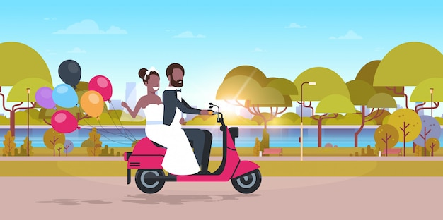 Just married couple riding motor scooter with colorful balloons   bride groom having fun wedding day concept park landscape background full length horizontal flat