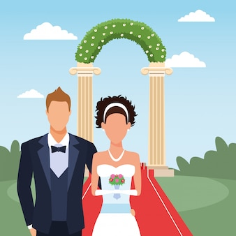 Just married couple standing over floral arch and landscape