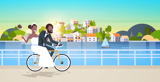 Just married man woman riding bicycle romantic   couple bride groom cycling bike having fun wedding day concept mountain city island background full length horizontal flat