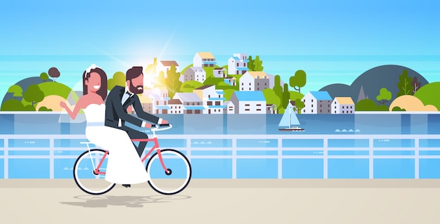 Just married man woman riding bicycle romantic couple bride and groom cycling bike having fun wedding day concept mountain city island sunset background full length horizontal