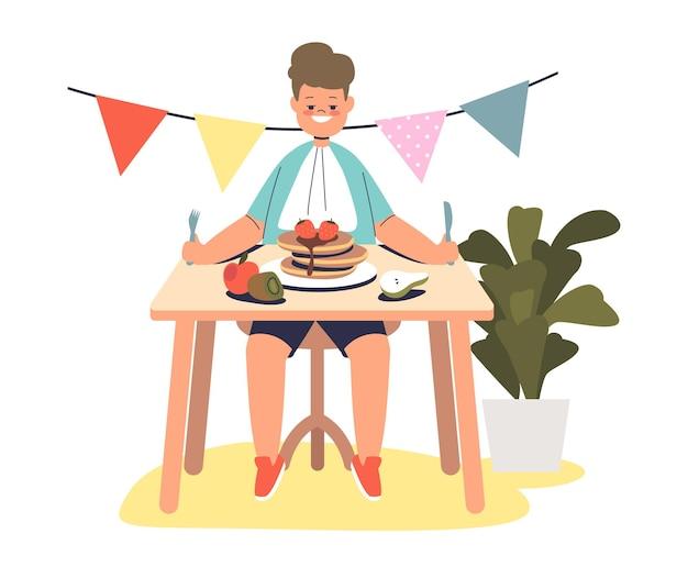 パンケーキを食べる男の子、テーブルに座って健康的な朝食の食事。小さな子供はおいしい食べ物を楽しむ