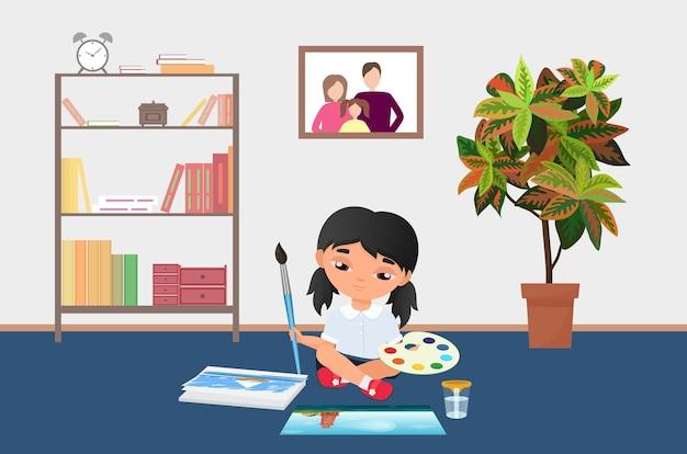 Kid painting with brush paints on palette girl artist sitting on kindergarten floor