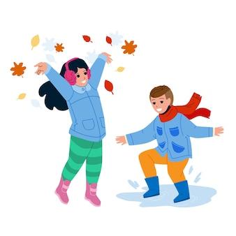 아이가 가 시즌 벡터에서 야외에서 함께 재생합니다. 웅덩이에서 점프하는 소년과 가을 나무를 던지는 초반 이었죠 소녀는 공원에서 나뭇잎. 평면 만화 그림 밖에서 함께 노는 캐릭터