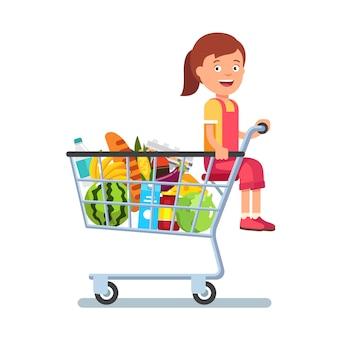 Ребенок сидит в корзине супермаркетов