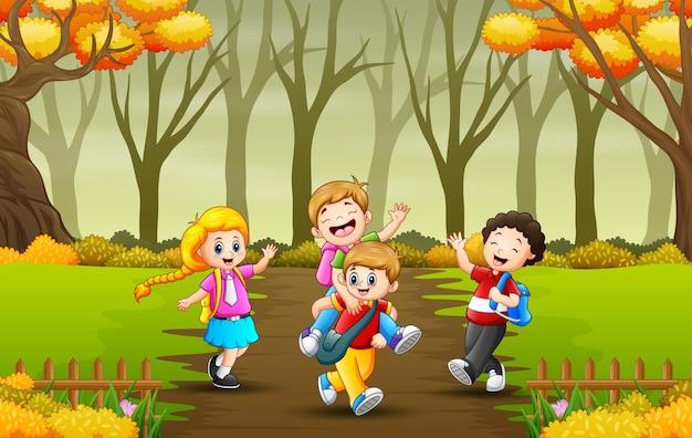 秋の森の小道を通って学校に通う子供たち