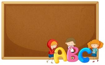 コルクボードにABCを保持している子供たち