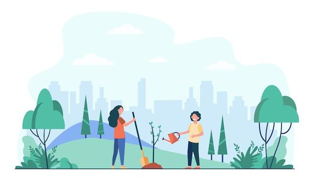 도시 공원에서 나무를 심는 아이. 야외에서 녹색 식물을 사용하는 원예 도구를 가진 아이들.