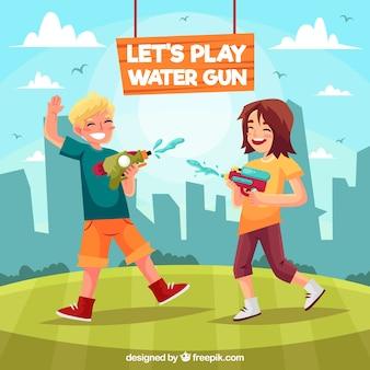 Bambini che giocano nel parco con pistole ad acqua in plastica